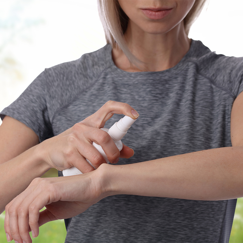 Woman spraying insect repellent on skin